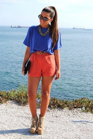 Cómo combinar: cartera sobre de cuero negra, botines con cordones de ante marrón claro, pantalones cortos rojos, blusa de manga corta azul
