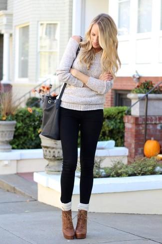 Cómo combinar: calcetines hasta la rodilla blancos, botines con cordones de cuero marrónes, vaqueros pitillo negros, jersey oversized gris