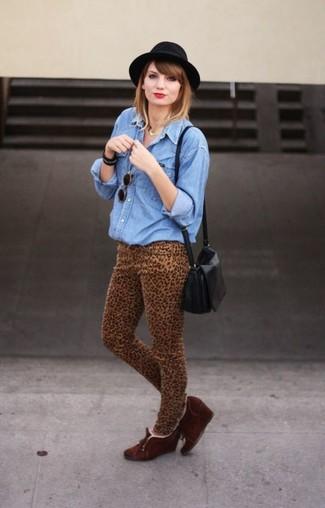 Cómo combinar: bolso bandolera de cuero negro, botines con cuña de ante en marrón oscuro, vaqueros pitillo de leopardo marrón claro, camisa vaquera azul