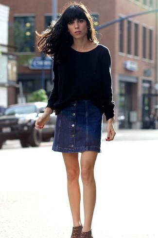 Cómo combinar: botines de ante de leopardo marrónes, falda con botones vaquera azul marino, jersey oversized negro