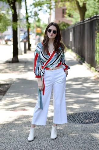Una falda pantalón de vestir con una blusa de manga larga en multicolor: Empareja una blusa de manga larga en multicolor junto a una falda pantalón para conseguir una apariencia relajada pero chic. Botines de cuero blancos son una opción excelente para complementar tu atuendo.