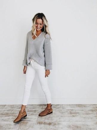 Outfits mujeres: Empareja un jersey de pico gris con unos vaqueros pitillo blancos para cualquier sorpresa que haya en el día. Botines de cuero con recorte marrón claro son una opción práctica para completar este atuendo.