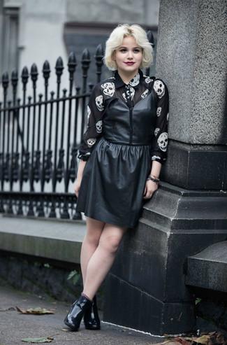 Cómo combinar: botines de cuero negros, camisa de vestir de gasa estampada en negro y blanco, vestido de tirantes de cuero negro