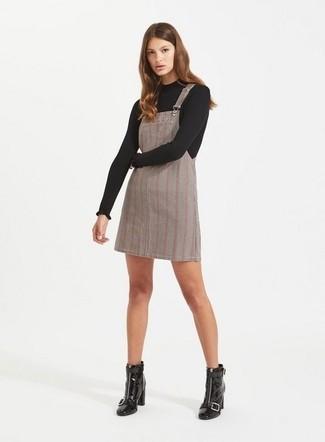 Cómo combinar: botines de cuero negros, pichi de tartán gris, jersey con cuello circular negro