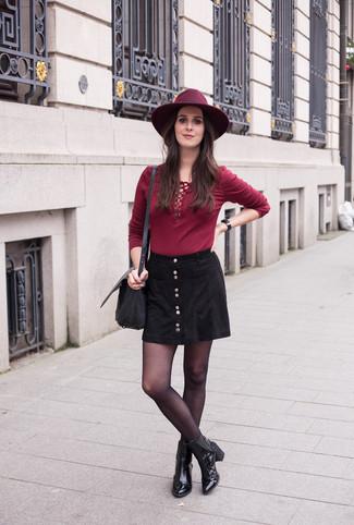 Cómo combinar: bolso bandolera de cuero negro, botines de cuero negros, falda con botones negra, camiseta de manga larga burdeos