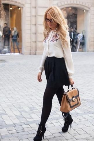 Cómo combinar: bolso de hombre de cuero marrón claro, botines de ante negros, falda skater negra, blusa de botones bordada blanca