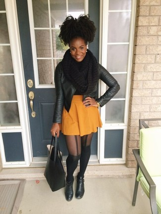Cómo combinar: bolsa tote de cuero negra, botines de cuero negros, falda skater naranja, chaqueta motera de cuero negra