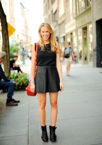 Cómo combinar: bolso bandolera de cuero rojo, botines de cuero negros, minifalda de cuero negra, blusa sin mangas negra