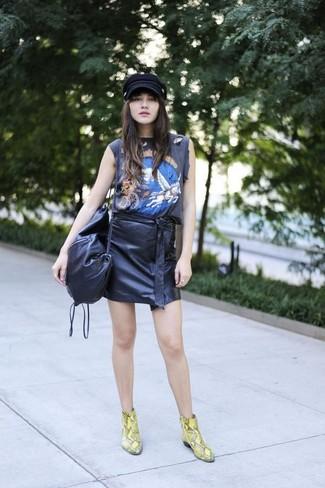 Cómo combinar: bolso bandolera de cuero negro, botines de cuero con print de serpiente amarillos, minifalda de cuero negra, camiseta sin manga estampada negra