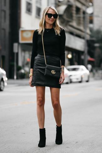 Cómo combinar: bolso bandolera de cuero negro, botines de ante negros, minifalda de cuero negra, jersey con cuello circular negro