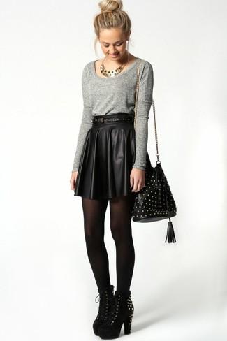 Cómo combinar: bolso bandolera de cuero con tachuelas negro, botines de ante con tachuelas negros, minifalda de cuero plisada negra, jersey con cuello circular gris