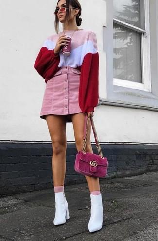 Cómo combinar: bolso bandolera de ante rosa, botines de cuero blancos, minifalda de pana rosada, jersey oversized de punto rosado