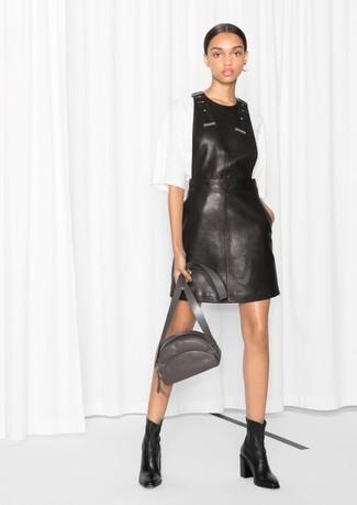 Cómo combinar: riñonera de cuero en gris oscuro, botines de cuero negros, blusa de manga corta blanca, pichi de cuero negro