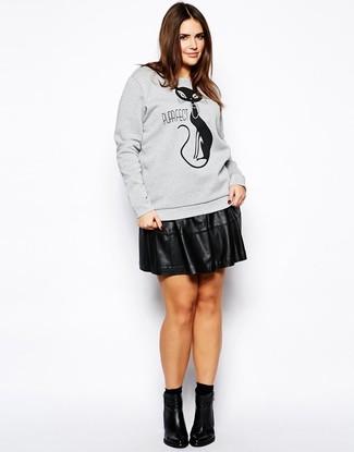 Cómo combinar: calcetines negros, botines de cuero negros, falda skater de cuero negra, sudadera estampada gris