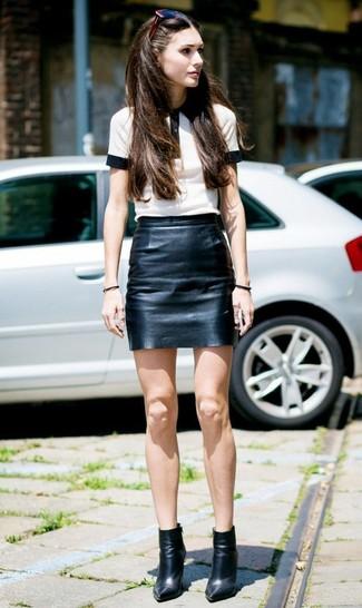 Cómo combinar: gafas de sol burdeos, botines de cuero negros, minifalda de cuero negra, camisa polo en blanco y negro