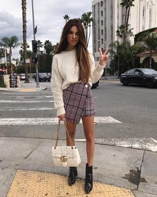 Combinar un jersey oversized de punto blanco: Emparejar un jersey oversized de punto blanco junto a una minifalda de tweed rosada es una opción excelente para el fin de semana. Botines de cuero negros son una opción incomparable para completar este atuendo.