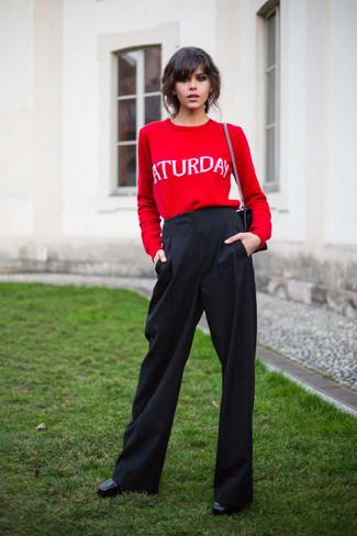 Cómo combinar: bolso de hombre de cuero acolchado negro, botines de cuero negros, pantalones anchos negros, jersey con cuello circular estampado rojo