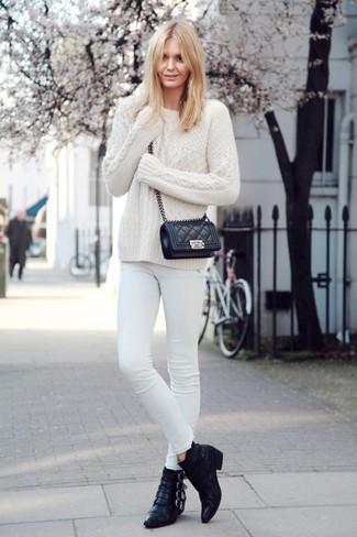 Cómo combinar: bolso bandolera de cuero acolchado negro, botines de cuero negros, vaqueros pitillo blancos, jersey de ochos blanco