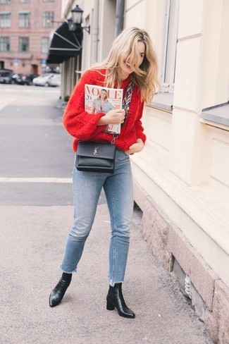 Cómo combinar: bolso bandolera de cuero negro, botines de cuero negros, vaqueros pitillo celestes, jersey oversized de punto rojo