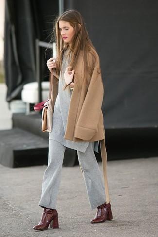 Cómo combinar: bolso bandolera de cuero en beige, botines de cuero marrónes, pantalones anchos de lana grises, túnica de lana gris