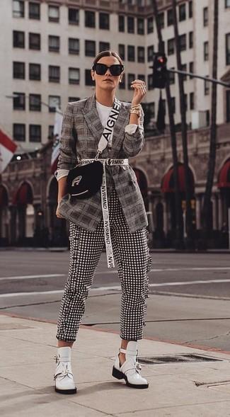 Cómo combinar: bolso bandolera de ante negro, botines de cuero con recorte blancos, pantalones pitillo de cuadro vichy en negro y blanco, blazer de tartán en marrón oscuro