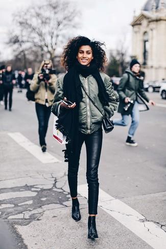 Cómo combinar: bolso bandolera de cuero negro, botines de cuero negros, pantalones pitillo de cuero negros, cazadora de aviador verde oliva