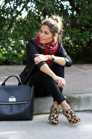 Cómo combinar: bolsa tote de cuero con tachuelas negra, botines de ante de leopardo marrón claro, pantalones pitillo negros, chaqueta motera de cuero con tachuelas negra