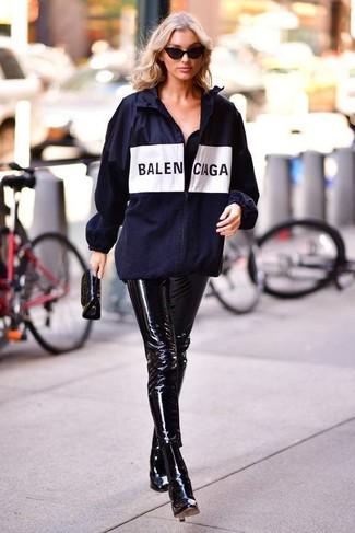 Cómo combinar: cartera sobre de cuero negra, botines de cuero negros, pantalones pitillo de cuero negros, chubasquero estampado azul marino