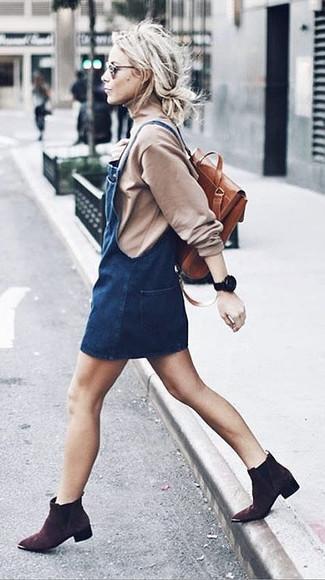 Cómo combinar: mochila de cuero en tabaco, botines de ante en marrón oscuro, pichi vaquero azul marino, jersey de cuello alto en beige