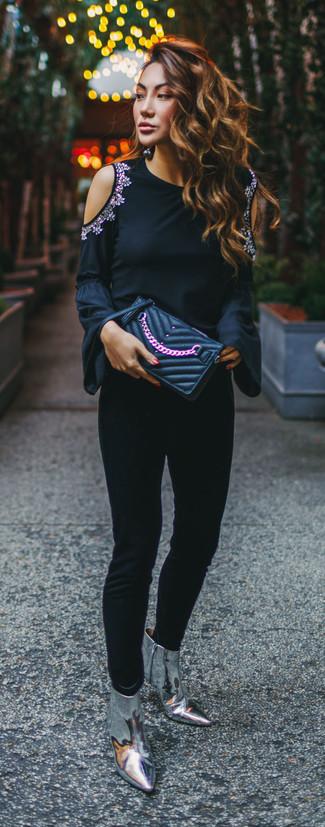 Cómo combinar: cartera sobre de cuero acolchada negra, botines de cuero plateados, pantalones pitillo negros, camiseta de manga larga con adornos negra