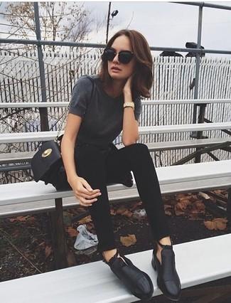 Cómo combinar: bolso bandolera de cuero negro, botines de cuero con recorte negros, vaqueros pitillo negros, camiseta con cuello circular en gris oscuro