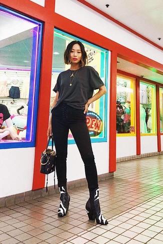 Cómo combinar: cartera de cuero negra, botines de cuero en negro y blanco, vaqueros pitillo negros, camiseta con cuello circular en gris oscuro