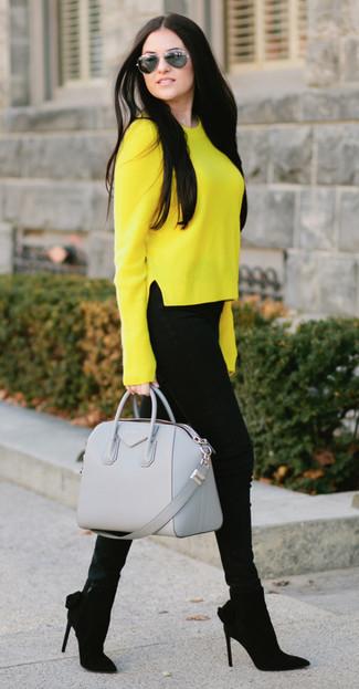 Cómo combinar: bolso de hombre de cuero gris, botines de ante negros, vaqueros pitillo negros, jersey con cuello circular amarillo