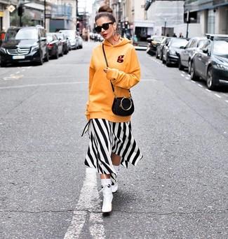 Cómo combinar: bolso bandolera de cuero negro, botines de cuero blancos, vestido midi de rayas verticales en blanco y negro, sudadera con capucha naranja