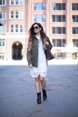 Cómo combinar: bolsa tote de cuero estampada en marrón oscuro, botines de cuero negros, vestido tubo de encaje blanco, chaqueta militar verde oliva