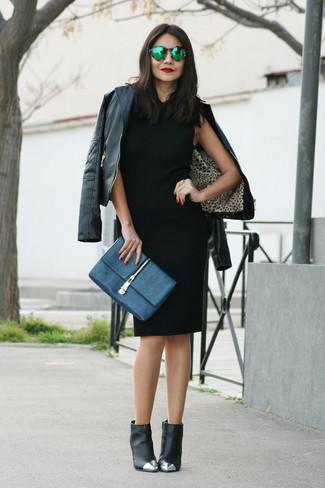 Cómo combinar: cartera sobre de cuero azul marino, botines de cuero con adornos negros, vestido tubo negro, chaqueta motera de cuero negra