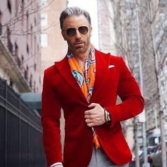 Cómo combinar: gafas de sol negras, bufanda estampada naranja, pantalón de vestir gris, blazer de terciopelo rojo