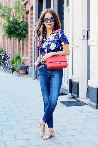 Cómo combinar: camisa de manga corta con print de flores azul, vaqueros pitillo azules, sandalias planas de cuero plateadas, bolso bandolera de cuero acolchado rojo