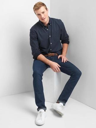 Cómo combinar: camisa de manga larga a lunares azul marino, vaqueros azul marino, tenis de cuero blancos, correa de cuero tejida marrón