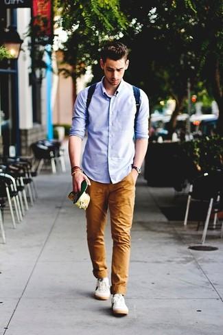 Una camisa de manga larga azul y un pantalón chino tabaco son prendas que debes tener en tu armario. Para el calzado ve por el camino informal con tenis blancos.