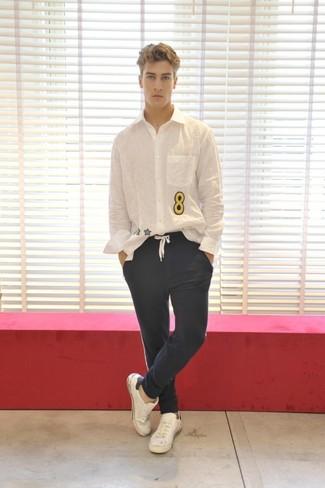 Look de moda: Camisa de manga larga estampada blanca, Pantalón chino azul marino, Tenis de cuero blancos