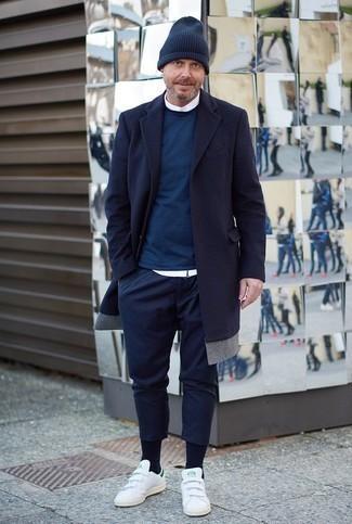 Combinar un abrigo largo azul marino: Opta por un abrigo largo azul marino y un pantalón chino azul marino para crear un estilo informal elegante. Mezcle diferentes estilos con tenis de cuero blancos.