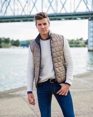Cómo combinar: vaqueros azules, camisa de manga larga azul marino, jersey con cuello circular blanco, chaleco de abrigo en beige