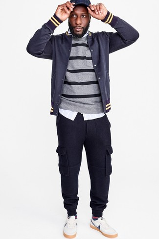 Cómo combinar: pantalón de chándal azul marino, camisa de manga larga de rayas verticales celeste, jersey con cuello circular de rayas horizontales gris, chaqueta varsity azul marino
