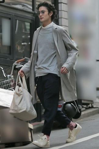 Outfits hombres: Intenta combinar una gabardina gris junto a un pantalón chino negro para las 8 horas. Tenis de cuero blancos añadirán un nuevo toque a un estilo que de lo contrario es clásico.