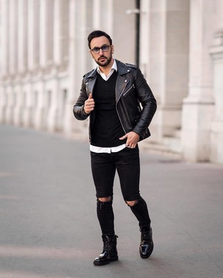 Cómo combinar: vaqueros pitillo desgastados negros, camisa de manga larga blanca, jersey de pico negro, chaqueta motera de cuero negra