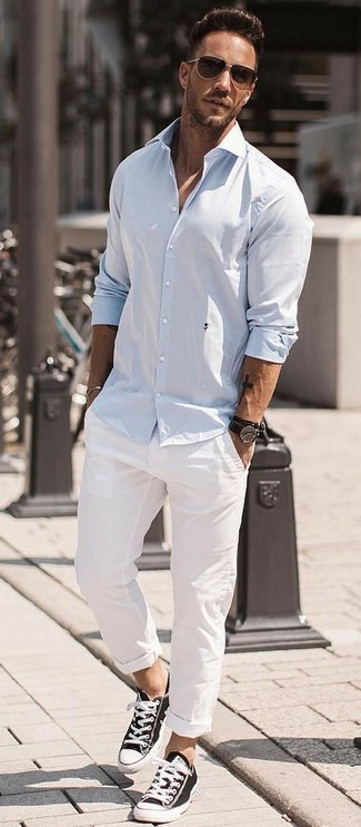 Emparejar una camisa de manga larga celeste y un pantalón chino blanco es una opción cómoda para hacer diligencias en la ciudad. ¿Por qué no añadir tenis de lona en negro y blanco a la combinación para dar una sensación más relajada?