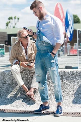 Cómo combinar: camisa de manga larga blanca, peto vaquero azul, zapatos derby de cuero azules, reloj de cuero en marrón oscuro