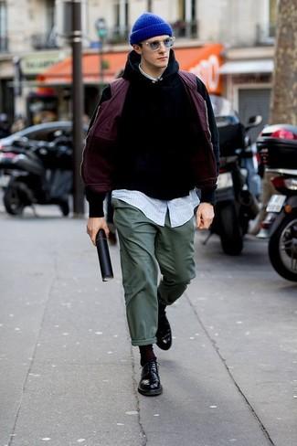 Cómo combinar: pantalón chino verde oscuro, camisa de manga larga de rayas verticales celeste, sudadera con capucha negra, chaleco de abrigo morado