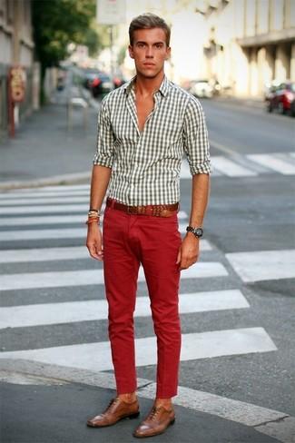 Cómo combinar: camisa de manga larga de cuadro vichy blanca, vaqueros rojos, zapatos brogue de cuero marrón claro, correa de cuero marrón